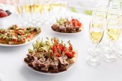 Bocadillos del pan de Rye, canapes, bruschetta en la placa blanca Banquete solemne Porción de vidrios champán o vino en la tabla fotografía de archivo libre de regalías