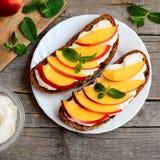 Bocadillos del pan de Rye con el queso cremoso, las nectarinas y la menta en una placa de la porción y en una tabla de madera del Fotografía de archivo libre de regalías