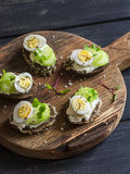 Bocadillos del queso con los huevos y el apio de codorniz en una tabla de cortar rústica Foto de archivo libre de regalías