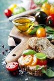 Bocadillos del tomate y de la albahaca con los ingredientes Imágenes de archivo libres de regalías