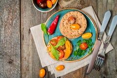 Bocadillos del tomate y del arugula con los ingredientes Fotografía de archivo