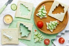 Bocadillos divertidos de la Navidad con el pan, rebanada del pepino, st del tomate Imagen de archivo libre de regalías