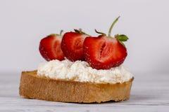 Bocadillos dulces con la fresa, el queso cremoso y la miel rojos frescos Imagen de archivo