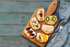 Bocadillos dulces en una tabla de madera verde vieja, visión superior, espacio de la copia Bocadillos de la fruta en una tabla de Fotografía de archivo