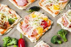 Bocadillos hechos en casa de la pizza en un papel de la hornada Foto de archivo libre de regalías