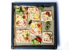 Bocadillos hechos en casa de la pizza en un papel de la hornada Fotos de archivo libres de regalías
