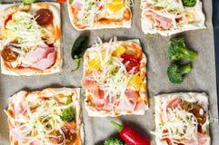 Bocadillos hechos en casa de la pizza en un papel de la hornada Imagen de archivo