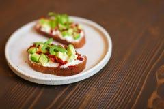 Bocadillos recién preparados con el aguacate, el pan de centeno, los tomates, concepto de comida sana, la nutrición y los ácidos  foto de archivo