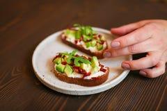 Bocadillos recién preparados con el aguacate, el pan de centeno, los tomates, concepto de comida sana, la nutrición y los ácidos  imagen de archivo libre de regalías