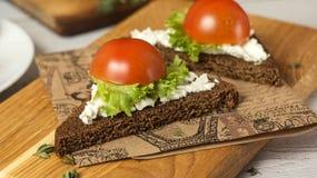 Bocadillos sanos de los bocados con el queso de cabra, ensalada, tomates de cereza Fotografía de archivo libre de regalías