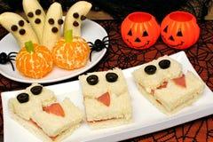 Bocadillos sanos del monstruo de Halloween, fantasmas del plátano y calabazas anaranjadas Fotografía de archivo