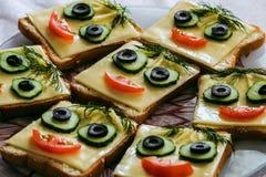 Bocadillos sonrientes divertidos con la cara de los pepinos, del tomate, de la aceituna y del eneldo Imagen de archivo libre de regalías
