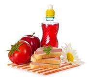 Bocadillos, tomate, manzana roja y botella Fotos de archivo libres de regalías