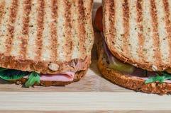 Bocadillos tostados con el jamón, el queso, los tomates y la ensalada en tabla de cortar de madera Foto de archivo libre de regalías