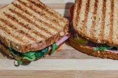 Bocadillos tostados con el jamón, el queso, los tomates y la ensalada en tabla de cortar de madera Foto de archivo