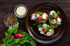 Bocadillos vegetarianos con el rábano, tomates de cereza, arugula, sésamo, semillas de lino, baguette curruscante blanco de la ap Fotos de archivo