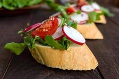 Bocadillos vegetarianos con el rábano, tomates de cereza, arugula, sésamo, semillas de lino, baguette curruscante blanco de la ap Imágenes de archivo libres de regalías