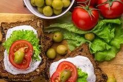 Bocadillos vegetarianos con pan de centeno sano, crema del queso, tomates, las aceitunas verdes y la lechuga en la tabla, visión  Foto de archivo