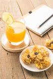 Bocado de la galleta de los cereales y zumo de naranja sano en vagos de madera de la tabla Fotografía de archivo libre de regalías