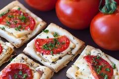 Bocado del hojaldre con queso Feta, tomates e hierbas Imagen de archivo