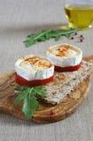 Bocado francés: Queso de cabra caliente en la rebanada de tomate y de biscote curruscante Imagen de archivo libre de regalías