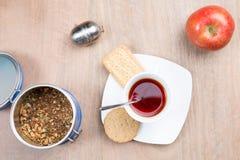Bocado por cuatro horas incluyendo las tortas secas una manzana y una taza de té Fotos de archivo libres de regalías