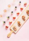 Bocados, bocadillos del brushetta, tiros del gazpacho, postres sobre fondo del rosa en colores pastel Imagen de archivo