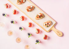 Bocados, bocadillos del brushetta, tiros del gazpacho, postres sobre fondo del rosa en colores pastel Fotos de archivo libres de regalías
