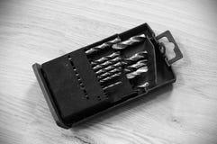 Bocados de broca em uma caixa plástica preta no assoalho estratificado foto de stock royalty free