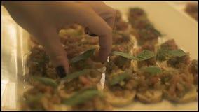 Bocados de la comida en la placa blanca en la tabla del partido Ciérrese encima de la mano femenina que toma los bocados apetitos almacen de metraje de vídeo