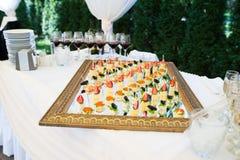 Bocados deliciosos en la tabla de la recepción nupcial en restaurante al aire libre de lujo Imágenes de archivo libres de regalías