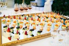 Bocados deliciosos en la tabla de la recepción nupcial en restaurante al aire libre de lujo Fotos de archivo libres de regalías