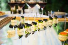 Bocados deliciosos en la tabla de la recepción nupcial en restaurante al aire libre de lujo Fotografía de archivo