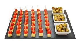 Bocados hechos con los pedazos del queso y del tomate en una bandeja negra cerca de tres cuencos con las aceitunas verdes fotos de archivo