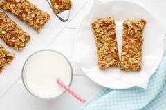 Bocados hechos en casa del cereal para la consumición sana Barras de Granola con leche en el fondo de madera blanco Foto de archivo