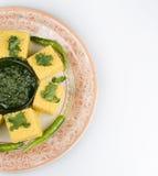 Bocados indios Dhokla con salsa picante verde Foto de archivo libre de regalías