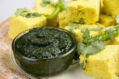 Bocados indios Dhokla con salsa picante verde imagen de archivo