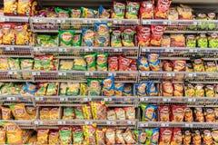 Bocados malsanos de los alimentos de preparación rápida en estante del supermercado Fotos de archivo
