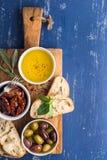 Bocados mediterráneos fijados Aceitunas, aceite, hierbas y pan cortado del ciabatta en tablero rústico amarillo del roble sobre p Imagenes de archivo