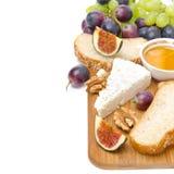 Bocados - queso, pan, higos, uvas, miel y nueces aislados Imagenes de archivo