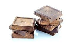 Bocados sanos sin azucarar oscuros de la barra de chocolate, aislados en el fondo blanco Fotos de archivo