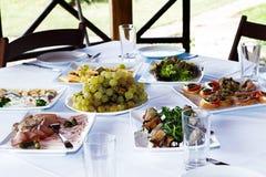 Bocados y comidas en la tabla con un mantel blanco imagen de archivo libre de regalías