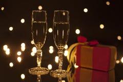 2 bocal с шампанским и подарочной коробкой на черной предпосылке с влиянием bokeh Стоковая Фотография