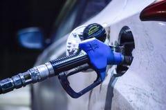 Bocal de abastecimento introduzido no tanque do carro branco no posto de gasolina TNK na trilha Borisoglebsk - Saratov, em dezemb fotos de stock