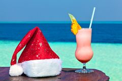 Bocal of drink is on a beach table with Santa hat Royalty Free Stock Photos