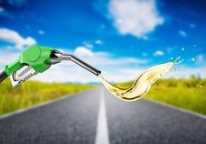 Bocal verde da bomba de gás com respingo do óleo na estrada da viagem Fotografia de Stock Royalty Free