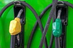 Bocas amarillas y verdes de la bomba de gas de la gasolina en una gasolinera Fotos de archivo