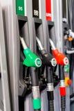 Bocas de relleno coloridas del surtidor de gasolina, gasolinera en un servicio Fotografía de archivo libre de regalías