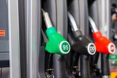Bocas de relleno coloridas del surtidor de gasolina, gasolinera en un servicio Foto de archivo