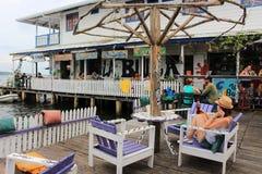 Bocas del托罗, Panamà ¡ - 8月,第10 2014年:游人和旅客享受饮料在Bocas del托罗市江边酒吧 免版税库存照片